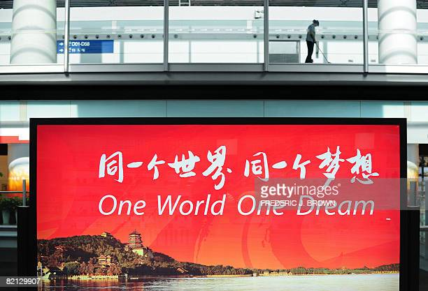 A cleaning lady cleans the floor above a billboard with an Olympics propaganda slogan and an image of Beijing's famed Summer Palace at Beijing...
