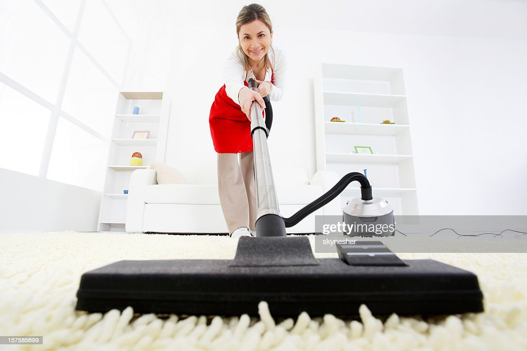 Cleaning lady vacuuming a soft carpet in living room. : Stock Photo