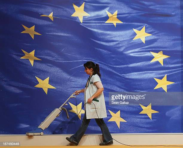 A cleaning lady vacuums next to the flag of the European Union while preparing for the German Christian Democratic Union federal party convention on...