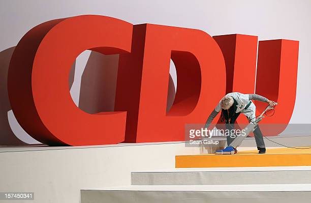A cleaning lady vacuums next to the logo of the German Christian Democratic Union while preparing for the CDU federal party convention on December 3...