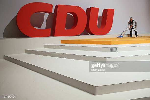 Cleaning lady vacuums next to the logo of the German Christian Democratic Union while preparing for the CDU federal party convention on December 3,...