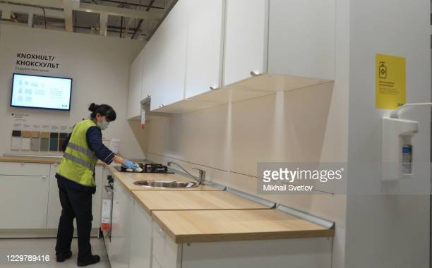 Cleaning lady wearing a protective wipes a kitchen set at the IKEA store on November 25, 2020 in Khimki in the suburbs of Moscow, Russia. The...