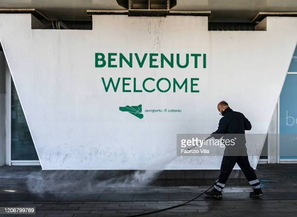 A cleaning man disinfecting the entrance to Catania airport during the Coronavirus emergency on March 12 2020 in Catania Italy The Coronavirus...