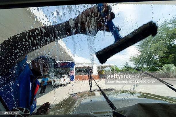 Cleaning mud and dead insects from a 4wd windscreen in a petrol station