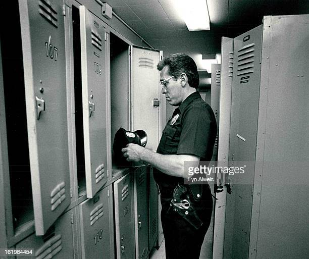 Cleaning out the old Denver Police substation District; Officer John Lopez finds a hat in a locker. Men started moving things out of the old building...