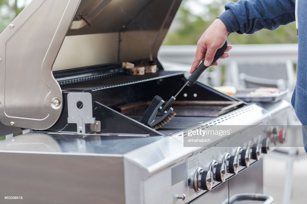 Cleaning outdoor gas grill : Stock Photo