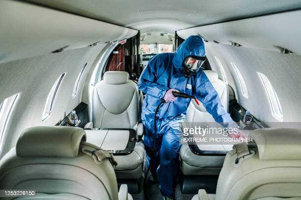a cleaning person in blue protective suit wiping down surfaces aboard an airplane before flight - department of health stock pictures, royalty-free photos & images