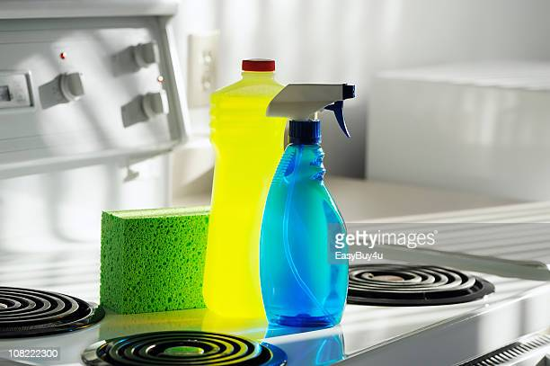 Cleaning Products and Sponge on White Kitchen Oven