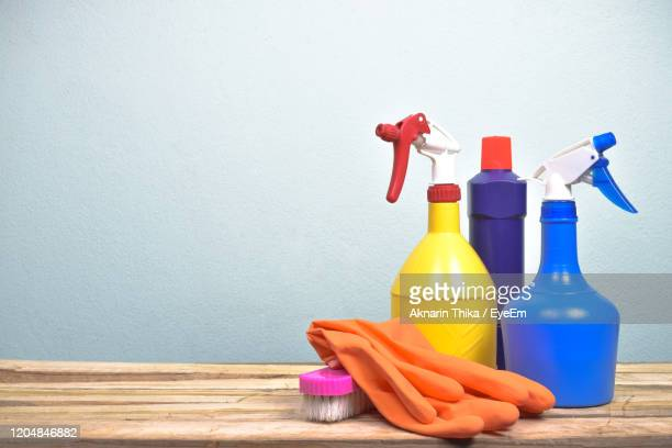 cleaning products on tablet against gray colored wall - cleaning agent stock pictures, royalty-free photos & images