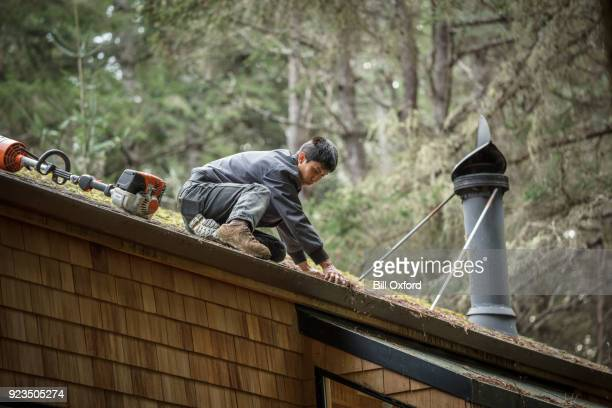 cleaning rain gutter on roof - roof gutter stock photos and pictures