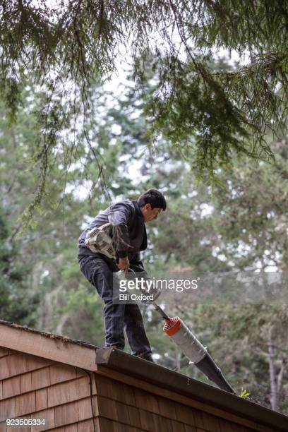 Cleaning rain gutter on roof