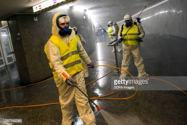Cleaning service workers wearing protective suits are seen disinfecting one of the most frequently used underpass in Warsaw. At night, the municipal...
