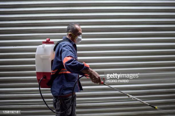 """Cleaning sprays disinfectant at the """"Central de Abasto"""" wholesale market, the biggest food supply central in Mexico City, on March 24, 2020 to fight..."""