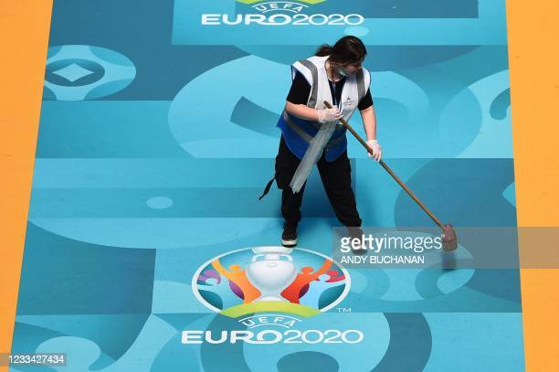 Cleaning staff member sweeps a walkway onto the pitch of Hampden Park and bearing the competition logo during the UEFA EURO 2020 European Football...