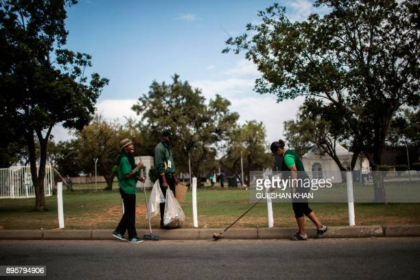 Cleaning staff sweep the street outside at the NASREC Expo Centre on the final day of the African National Congress in Johannesburg on December 20,...