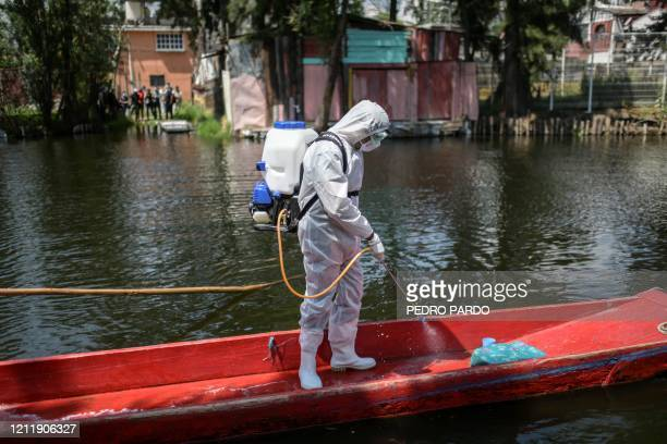 TOPSHOT Cleaning staff wearing personal protective equipment disinfects a boat at the Xochimilco lake in Mexico City on May 5 amid the new...