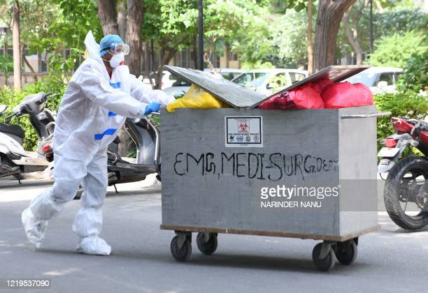 A cleaning staffmember carries dustbins filled with medical waste from COVID19 patients into a trash bin at Guru Nanak Dev Hospital after the...
