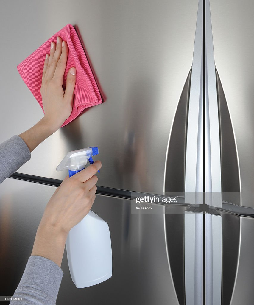 Cleaning surface of refrigerator : Stock Photo