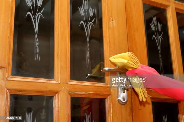 cleaning the doorknob with yellow fabric duster while wearing red color rubber gloves. - glove stock pictures, royalty-free photos & images