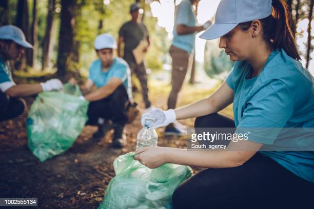 cleaning the environment together - dedizione foto e immagini stock