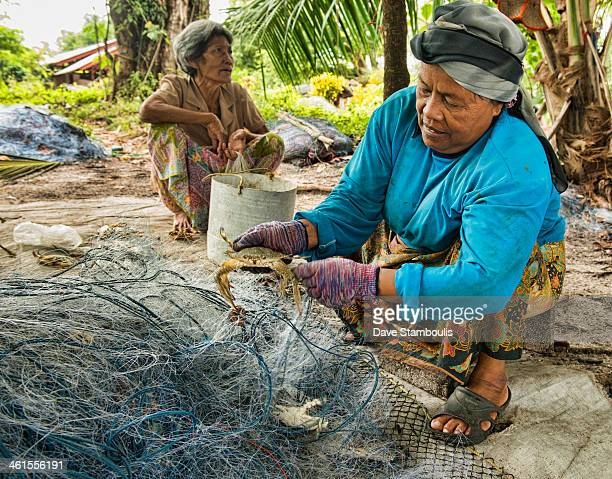 Cleaning the fishing nets in the crab market on Koh Lanta island in Thailand