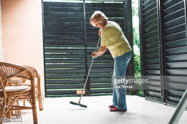 cleaning the floor with a broom - sweeping stock pictures, royalty-free photos & images