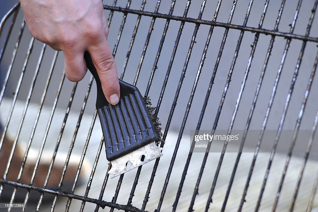 cleaning the grill with scrubber - Grillbürste : Stock Photo
