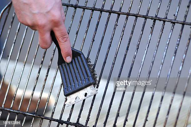 cleaning the grill with scrubber - grillbürste - grill concept stock photos and pictures