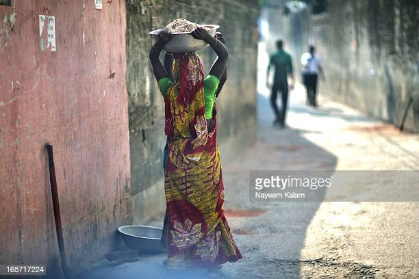 CONTENT] Cleaning the soil and rubble carrying them repairing the road women can do it all Two labourers in front of my car and our house this...
