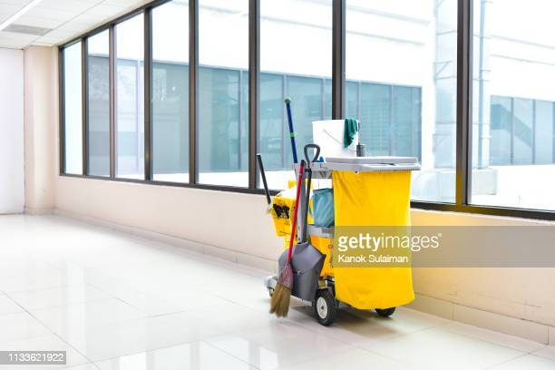 cleaning tools cart wait for cleaning,yellow mop bucket and set of cleaning equipment in the airport - janitorial services stock photos and pictures