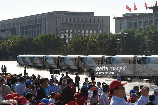 Cleaning trucks sweep the roads on the parade route in front of guests in Tiananmen Square ahead of a military parade later in the morning in Beijing...