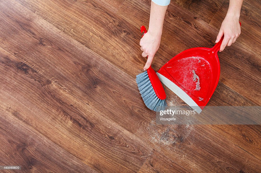Cleaning woman sweeping wooden floor : Stock Photo
