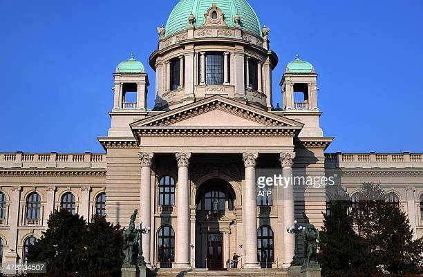 Cleaning woman wipes the entrance of the Serbian parliament building on March 12, 2014. Voters in Serbia go to the snap polls on Sunday with the...