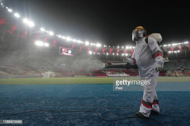 Cleaning worker disinfects to prevent spread of COVID-19 during a round of sixteen second leg match between Flamengo and Racing Club as part of Copa...