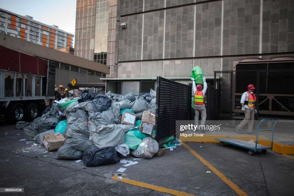 Cleaning workers carry documents to the garbage depot at the PEMEX administrative building on February 01, 2013 in Mexico City, Mexico. Pemex is stepping up security at oil production facilities as authorities investigate a blast that killed at least 33 people at the state-owned company's headquarters in Mexico City.
