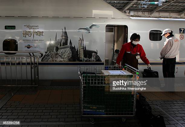 Cleaning workers of JR West Sanyo Shinkansen Line remove bags from train car which features the Hogwarts Castle and Harry Potter's pet owl Hedwig on...