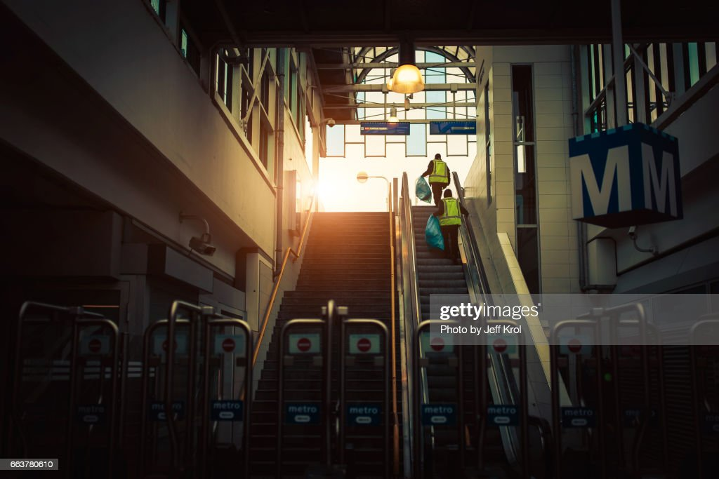 Cleaning workers walking up the stairs in a metro/subway underground station. Sunlight at the end, in a cinematic scene. : Stock Photo