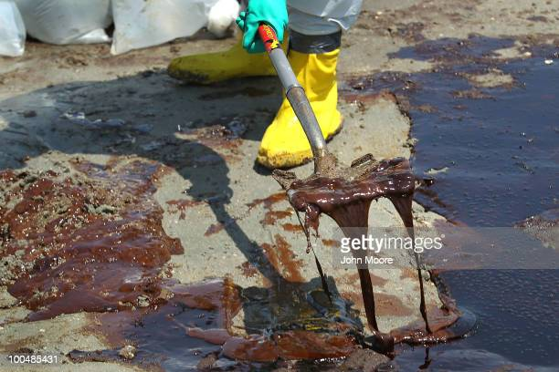 BP cleanup crew shovels oil from a beach on May 24 2010 at Port Fourchon Louisiana BP CEO Tony Hayward who visited the beach said that BP is doing...