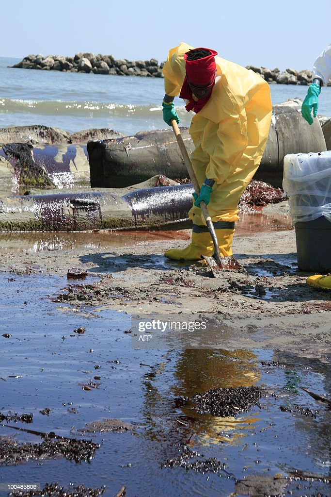 A BP cleanup crew shovels oil from a beach on May 24, 2010 at Port Fourchon, Louisiana. Under-fire BP chief executive Tony Hayward admitted at a press conference on the beach that the British energy giant's reputation was on the line over the oil spill in the Gulf of Mexico. AFP PHOTO/Stephane JOURDAIN