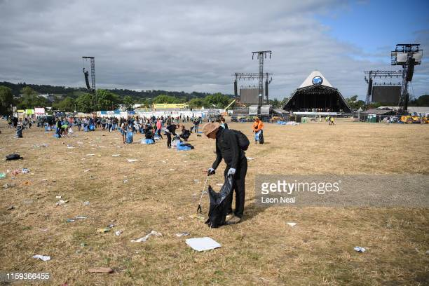 Clean-up crews clear litter and debris from the area in front of thePyramid Stage on the morning after the final night of the Glastonbury Festival at...