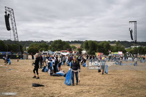 Cleanup crews clear litter and debris from the area in front of thePyramid Stage on the morning after the final night of the Glastonbury Festival at...