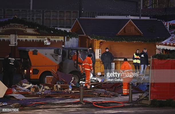 Cleanup crews collect the wrecked remains of the Christmas market stand where two days before a man drove a heavy truck into the market in an...