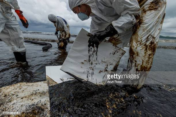rayong, thailand - july 31, 2013: cleanup crews fill bags with oiled sand and debris after a pipeline spilling oil into an environmentally sensitive area at ao prao beach, samet island. - hydrocarbon stock pictures, royalty-free photos & images