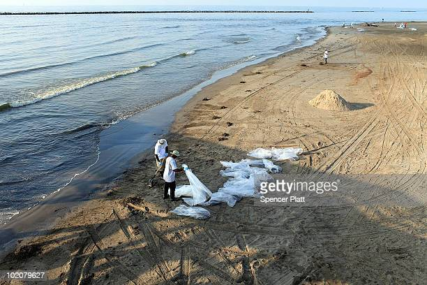 Cleanup workers collect oilcontaminated sand along a beach June 14 2010 in Grand Isle Louisiana The BP spill has been called the largest...