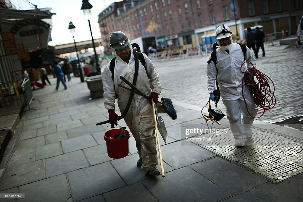 Clean-up workers walk down a street in the heavily damaged South Street Seaport affected by Superstorm Sandy on December 3, 2012 in New York City. South Street Seaport, an area popular with tourists which was about to go through a major redevelopment, suffered severe damage from Hurricane Sandy. Most of the buildings and businesses, including the South Street Seaport Museum, suffered severe flooding and remained closed. According to a new Siena Research Institute poll, most New Yorkers overwhelmingly agree that climate change was behind Hurricane Sandy.