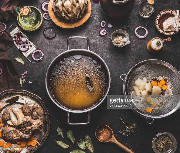 clear beef bone broth or stock without meat in cooking pot on kitchen table - gravy stock photos and pictures
