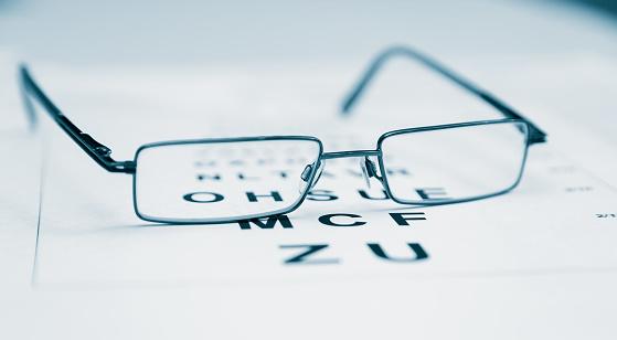 Clear Black modern glasses on a eye sight test chart.. 1061815634