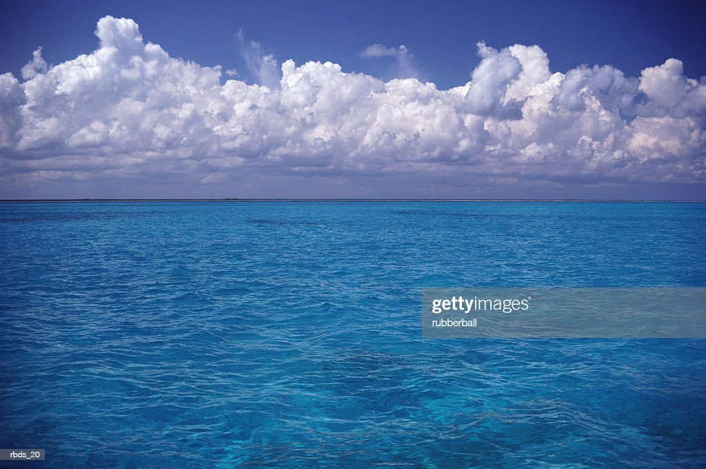 clear blue island waters with white clouds on the horizon : Stockfoto