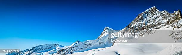 Clear blue skies over snowy Alps mountain peaks Jungfrau Switzerland