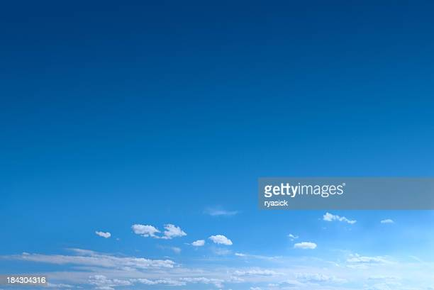 clear blue sky background with scattered clouds - heldere lucht stockfoto's en -beelden